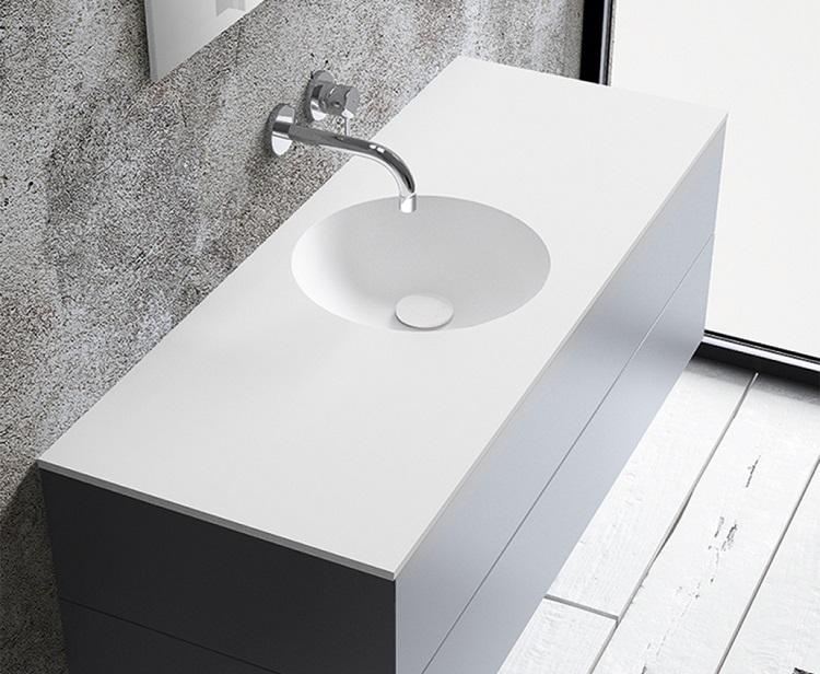 Biała umywalka wpuszczona w blat, w zestawie z szafką. Przykład nowoczesnej aranżacji przestrzeni łazienkowej.