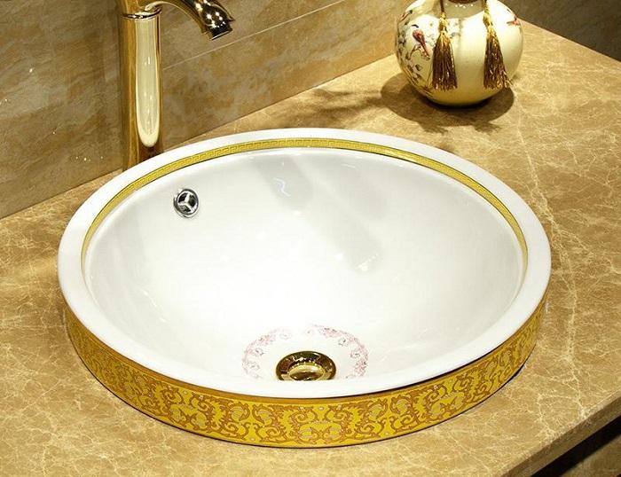 ceramiczna umywalka owalna, wpuszczana w kamienny blat łazienkowy, z charakterystycznym wzornictwem na zewnętrznej ścianie i dnie misy