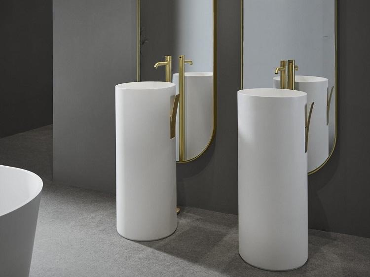 dwie umywalki wolnostojące Giro Ibani, o owalnych kształtach i w białym kolorze, z lustrem łazienkowym umieszczonym w orientacji pionowej