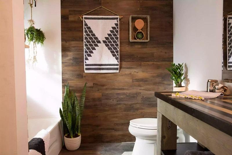 łazienka w stylu skandynawskim z białymi elementami armatury (stojąca muszla klozetowa), panelami drewnopodobnymi i drewnianym blatem łazienkowym oraz świetnie komponującymi się z wnętrzem roślinami (akcenty zieleni)