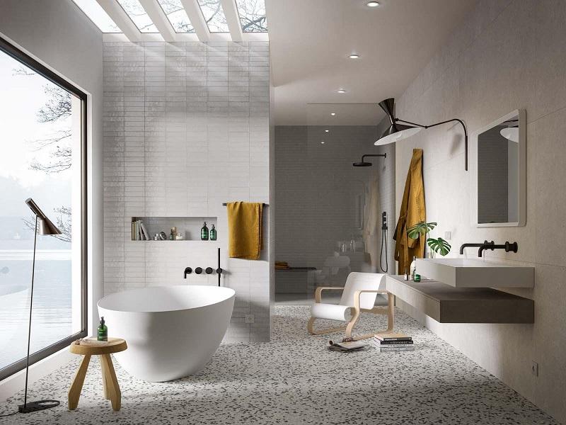 minimalistyczne wykorzystanie dużej przestrzeni łazienkowej, z wanną wolnostojącą oraz umywalką w kolorze białym, delikatnymi wzorami na ścianach w odcieniach szarości oraz mozaiką podłogową
